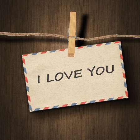 instant film transfer: text I love you on the old envelope and clothes peg wood background