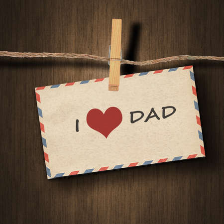 instant film transfer: text I love dad on the old envelope and clothes peg wood background