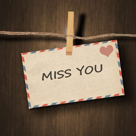 miss you: text miss you on the old envelope and clothes peg wood background Stock Photo