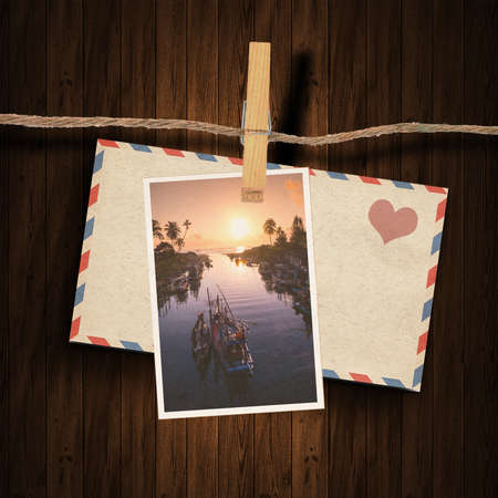 the old envelope , postcard and clothes peg wood background photo