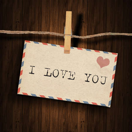 text i love you  on the old envelope and clothes peg wood background