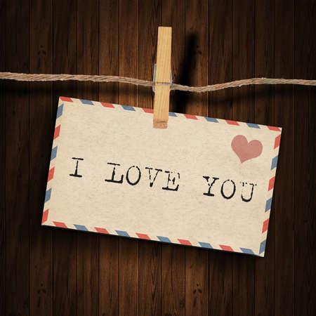 te amo: texto te amo en el sobre de edad y la clavija de ropa de madera de fondo