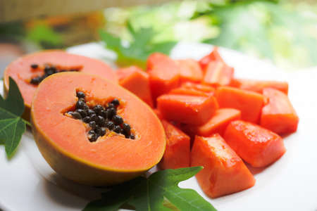 sweet papaya on the dish with green papaya leaf Stock Photo