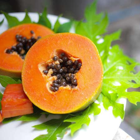 cranny: sweet papaya on the dish with green papaya leaf Stock Photo