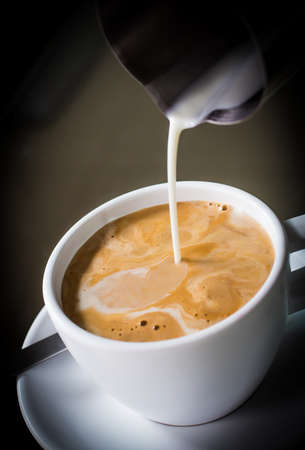 Pouring cream into a cup of coffee Standard-Bild