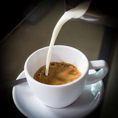 creamer: Pouring cream into a cup of coffee Stock Photo
