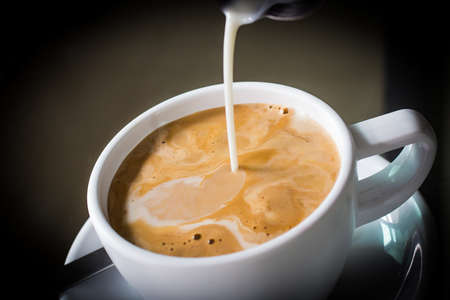 Pouring cream into a cup of coffee 版權商用圖片