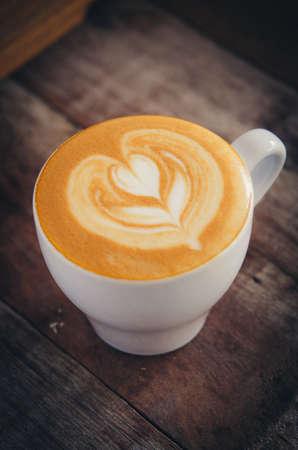 Marco shot coffee latte art on the wood desk vintage style color tone