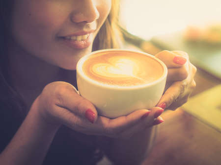 Beautiful Girl Drinking Tea or Coffee in vintage color toned style photo