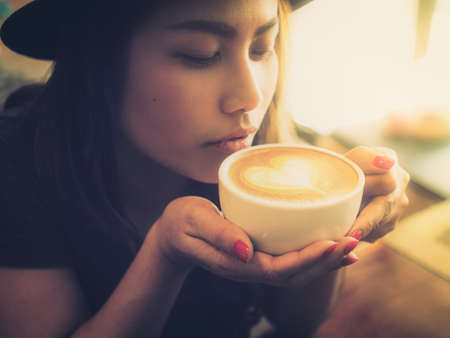 Beautiful Girl Drinking Tea or Coffee in vintage color toned style