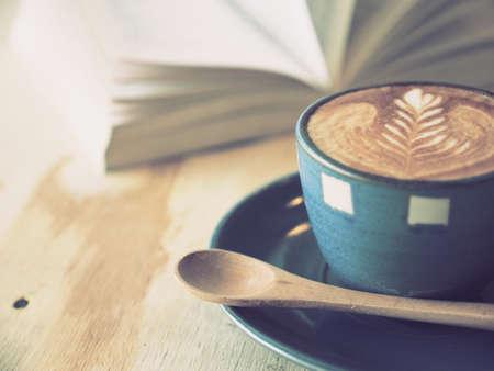 kopje koffie latte art met boek in koffiewinkel vintage kleur