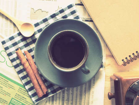 cup of coffee on the wood desk with business newspaper in vintage color toned photo