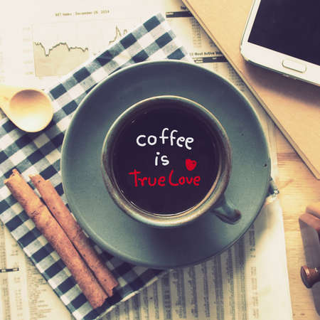 text coffee is true love in cup of coffee on the wood desk with business newspaper in vintage color toned photo