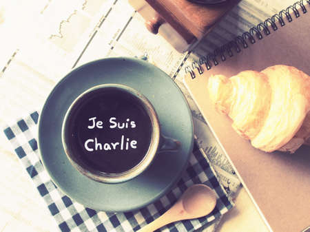 Text Je suis charlie on the cup of coffee on the wood desk with business newspaper in vintage color toned photo