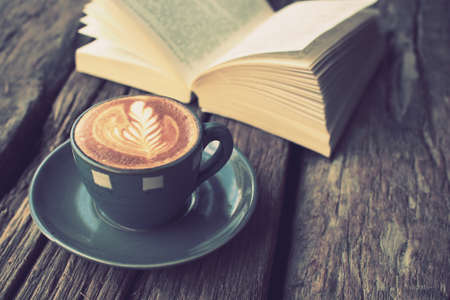 cup of coffee latte art on the wood desk and book in vintage color tone
