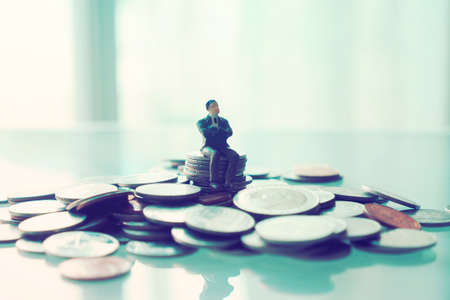 miniature businessman sitting on the coin : concept idea about making money with internet e-commerce photo