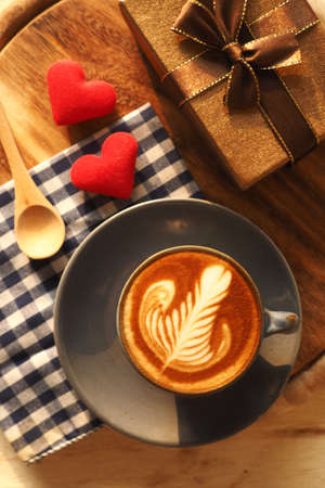 vintage color tone of  cup of coffee with red heart on the table coffee shop Standard-Bild