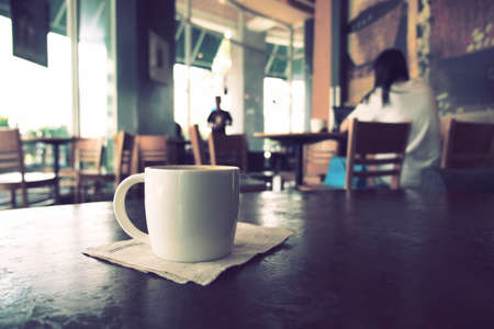 friends at bar: vintage color tone of  cup of coffee  on the table coffee shop