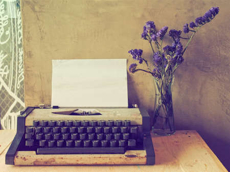 vintage typewriter on the wood texture background with vintage color tone 스톡 콘텐츠