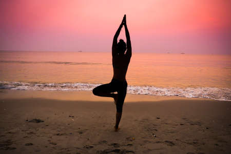 Silhouette young woman practicing yoga on the beach at sunrise