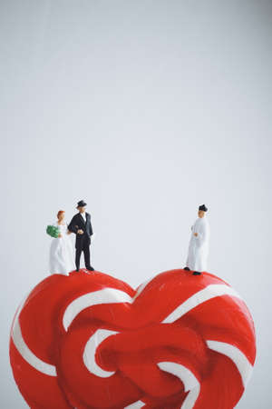 minature: mniature people : groom and bride wedding on heart lollipop white background