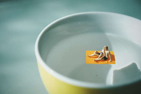 miniature people : man and woman relax on the coffee cup