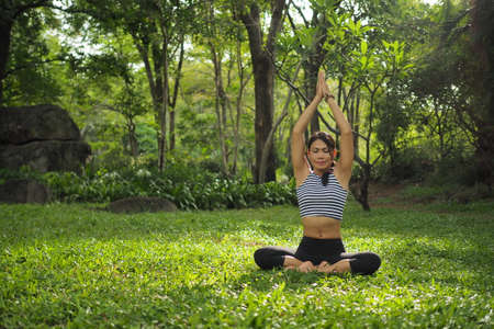 Young woman doing yoga exercises in the garden park Stock Photo - 43094289