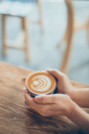 cappaccino: woman hand with cup of coffee latte art on the wood desk in vintage color tone Stock Photo