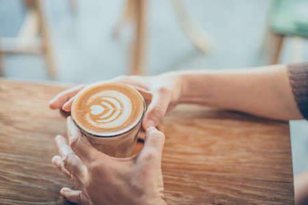 gaffe: woman hand with cup of coffee latte art on the wood desk in vintage color tone Stock Photo
