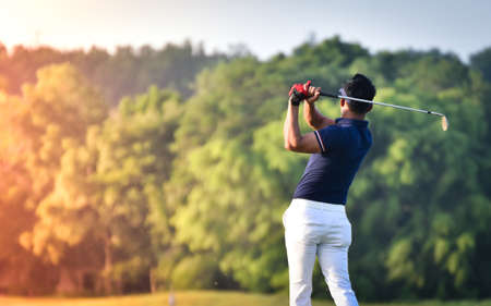 shot: Golfer hitting golf shot with club on course vintage color tone