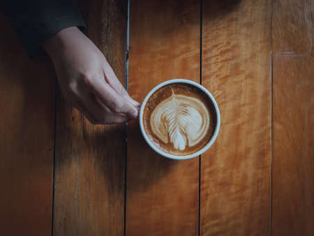 coffee latte art in coffee shop wood texture background with woman hand in vintage color tone
