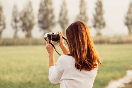 Beautiful Asian woman holding vintage camera in hand and standing over moutain background,traveler concept.