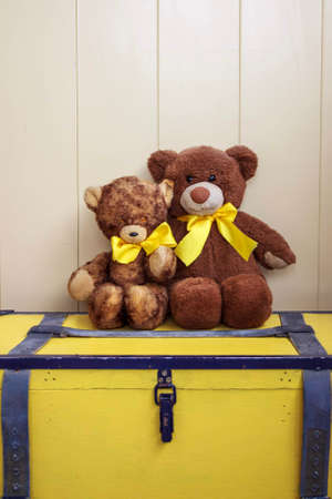 Two old bears sitting together on a yellow vintage chest.