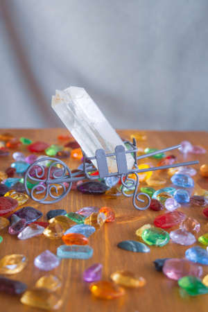 Quartz crystal on a wooden surface with multicolored glass cabochons