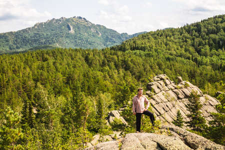 Man standing on top of a mountain. Trees growing from stone. Altai region, Russia.