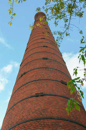 Old brick pipe factory against a blue sky and green leaves. Imagens