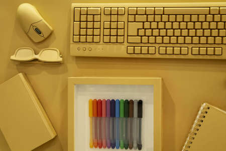 Office accessories including keyboard, laptop mouse, glasses, notebook and felt-tip pens on a yellow background. Standard-Bild - 138443461