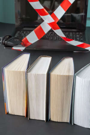 Gadget detox concept. Digital addiction concept. Books in the foreground. Stock Photo