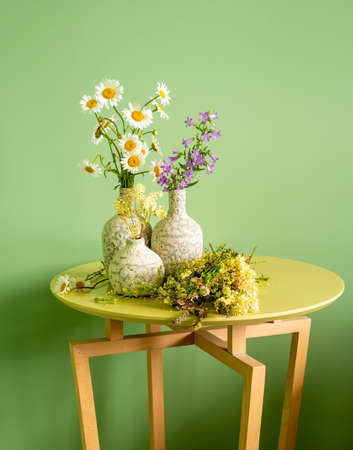 Three ceramic vases with wildflowers on a table