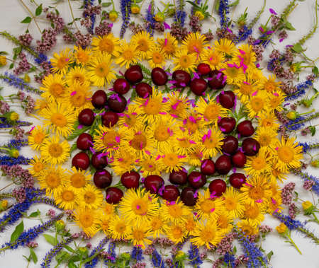 Arrangement of yellow and blue wildflowers and cherries