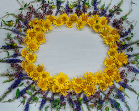 Arrangement of yellow and blue wildflowers on a wooden surface