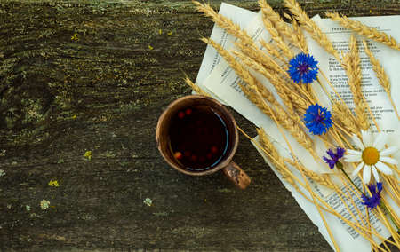 Autumn still life with a cup of tea, ears of wheat, cornflowers on a rustic wooden background.