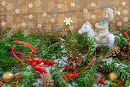 Christmas composition with fir branches, cones, berries and a toy - a bear on a horse