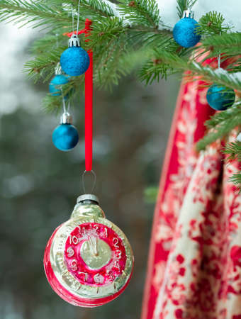 Retro clock Christmas toy on a Christmas tree in a winter forest 版權商用圖片