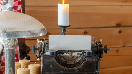 Old typewriter with white sheet of paper on the table with candles and table lamp