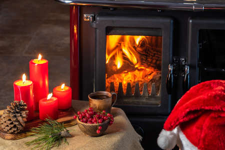 In front of a wood burning stove, a table with red candles, a cup and a red berry and a man in a red cap Stock Photo