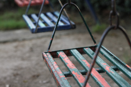 sway: empty painted steel swings in public playground Stock Photo
