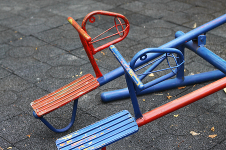 teeter: blue and red horse shaped seesaws in public playground