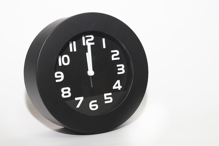 12 o'clock: table clock telling time at 12 oclock, isolated on white background Stock Photo