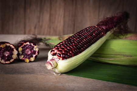 Siam Ruby Queen is super sweet corn with red color, can be eaten fresh place overlap and place on banana leaf and wood table background